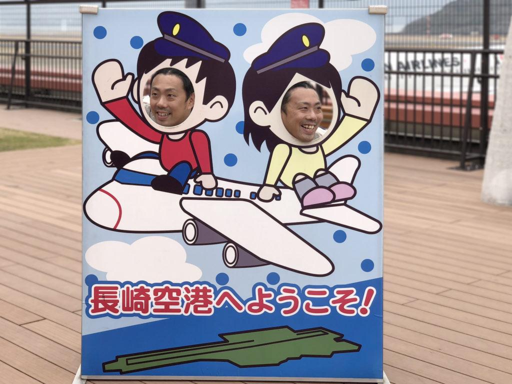 長崎の空の玄関口「長崎空港」の展望デッキで飛行機に乗る二人の顔ハメ